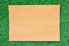 Brown-Papier auf grünem Gras Stockfotos
