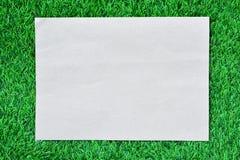 Brown-Papier auf grünem Gras Stockfotografie