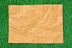 Brown-Papier auf grünem Gras Stockbild