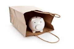Brown-Papier-Einkaufstasche und Piggy Querneigung lizenzfreie stockbilder