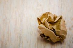 Brown-Papierball auf hölzernem Hintergrund Lizenzfreie Stockfotos