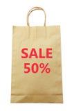 Brown-Papiereinkaufstasche mit dem Text des Verkaufs 50% lokalisiert auf weißem Hintergrund (Beschneidungspfad) Stockbild