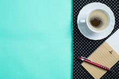 Brown-Papiernotizblock mit Stift und Kaffee in der weißen Schale auf schwarzem Sc Lizenzfreie Stockfotografie