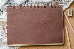 Brown-Papiertagebuch mit Bleistiften und Bleistiftspitzer auf hölzernem Ba Stockfoto