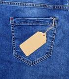 Brown papieru pusta metka na arkanie przeciw tylnej kieszeni niebiescy dżinsy zdjęcie stock
