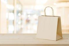 Brown papieru torba na zakupy na drewno stole nad zamazanym sklepu backgr Obrazy Royalty Free