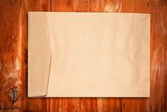 Brown-Papierumschlag auf Holz Lizenzfreie Stockbilder