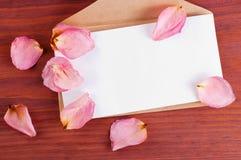 Brown-Papierumschlag mit dem leeren weißen verzierten Blatt zerstreute rosafarbene Blumenblätter auf Holztisch mit Raum für Text Lizenzfreie Stockfotos