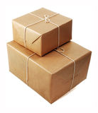 Brown parcels. Brown paper parcels ready to be shipped brightly lit on isolated white background royalty free stock images