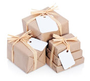 Brown parcels with blank label. Closeup of parcels in brown wrapping paper and blank tags or labels, isolated on white background Stock Photos