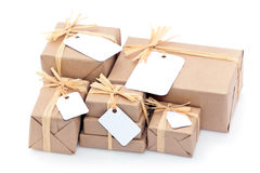 Brown parcels with blank label. Closeup of parcels in brown wrapping paper and blank tags or labels, isolated on white background stock photo