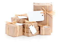 Brown parcels with blank label. Closeup of parcels in brown wrapping paper and blank tags or labels isolated on white background Stock Photo