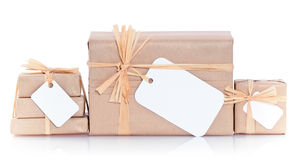 Brown parcels with blank label. Closeup of parcels in brown wrapping paper and blank tags or labels, isolated on white background Royalty Free Stock Photo