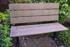 Brown parkowa ławka dla odpoczynku w ogrodowym położeniu Obraz Stock