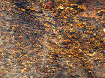 Brown pebbles in a river with ripples and reflections Royalty Free Stock Photos