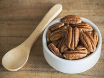 Brown pecans in white Bowl on a wood table. Royalty Free Stock Images