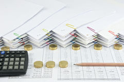 Brown pencil with black calculator between Pile of gold coins. And pile of paperwork as background royalty free stock image