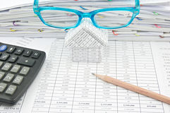 Brown pencil and blue glasses on house with finance account Stock Image