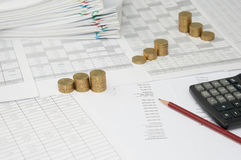 Brown pencil and calculator on balance sheet with gold coins. Brown pencil and calculator with step pile of gold coins on the statement finance account have blur stock photo