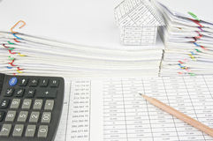 Brown pencil and calculator on finance account. Have house place on pile of paperwork as background stock photos