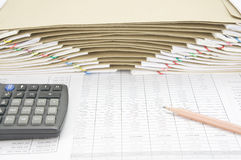 Brown pencil with calculator have envelope between paperwork as background. Brown pencil with calculator on finance account have brown envelope between overload stock photos