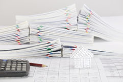 Brown pencil with calculator and house on finance account. Have blur pile overload paperwork of report and receipt with colorful paperclip place on white stock images