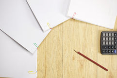 Brown pencil with calculator and stack paperwork of finance account. Place on wood background Stock Image