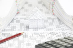 Brown pencil on finance account with blur calculator. Brown pencil on finance account have blur calculator and blur house with pile of document as foreground and stock images