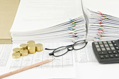 Brown pencil and gold coins with spectacles and calculator Stock Image