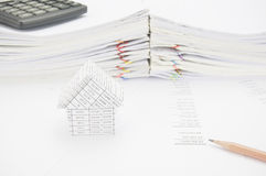 Brown pencil and house on balance sheet Stock Image