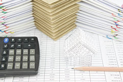 Brown pencil and house with calculator on finance account. Have pile of envelope between paperwork as background stock image