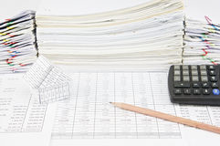 Brown pencil and house with calculator. On finance account have pile of paperwork as background royalty free stock photo