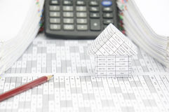 Brown pencil and house on finance account with blur calculator. Brown pencil and house on finance account have blur calculator with pile of document as royalty free stock images