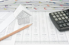 Brown pencil near house and calculator on finance account. With pile of paperwork as background Royalty Free Stock Photos