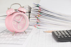 Brown pencil and old pink alarm clock on finance account. Have blur calculator and pile overload paperwork of report and receipt with colorful paperclip as Royalty Free Stock Images