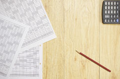 Brown pencil and paperwork of finance account with calculator. Place on wood background stock images