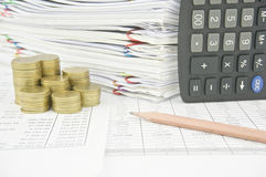 Brown pencil put near stack gold coins and calculator. On finance account with pile of paperwork as background stock photography