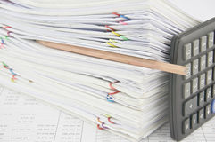 Brown pencil put in stack paperwork with vertical calculator. On finance account with pile of paperwork as background Royalty Free Stock Image