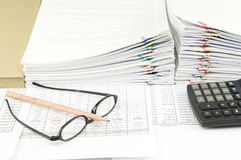 Brown pencil on spectacles and calculator. Have pile of paperwork as background royalty free stock photo