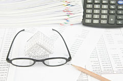 Brown pencil with spectacles and house on balance sheet Stock Images