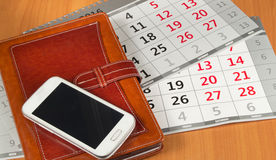Brown personal organizer or planner with a mobile phone and a calendar on the desktop Royalty Free Stock Images