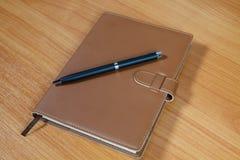 Brown pióro nad drewnianym i notatnik Obrazy Stock