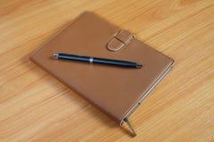 Brown pióro nad drewnianym i notatnik Fotografia Royalty Free