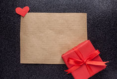 Brown piece of paper and red gift. Brown craft piece of paper and red gift black background Royalty Free Stock Photo