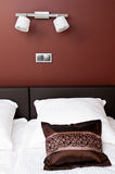 Brown pillow on bed with wall lighting Stock Photography