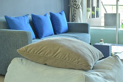 Brown pillow on beige fabric cubic stool with blue sofa Stock Photo