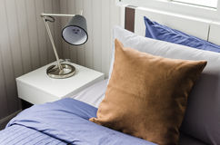 Brown pillow on modern bed with lamp Stock Photos