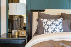 A brown pillows on bed with brown blanket and luxury lamp on woo. Den table with green wall in bedroom Stock Photos