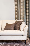 Brown pillows on empty beige sofa Stock Photography