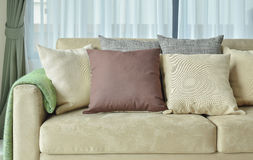 Brown pillows on light brown leather sofa Royalty Free Stock Photos